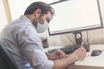 Un homme masqué travaille devant son ordinateur