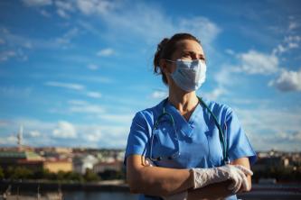 Une infirmière masquée, les bras croisés, regarde l'horizon