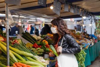 Une femme porte un masque sur un marché