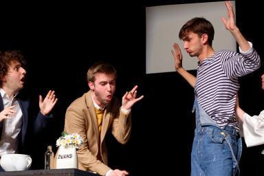 plusieurs comédiens sur scène, dont un les bras levés