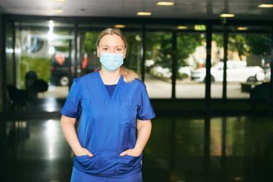 Une étudiante avec une blouse de soignant et un masque se tient debout dans un hall