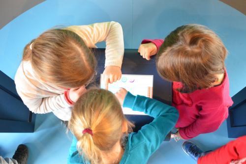vue plongeante sur des enfants au-dessus d'une tablette tactile à l'Écopole Edelweiss